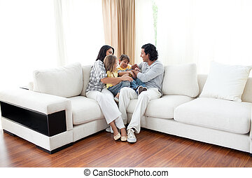 Jolly family watching TV on sofa in the living room