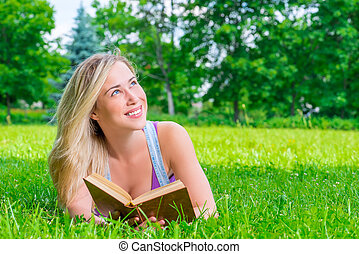 happy dreamy girl reading a book in the park