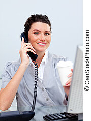 Confident business woman using a phone in her office