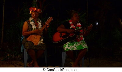 Women play on ukulele and guitar - Two mature pacific...