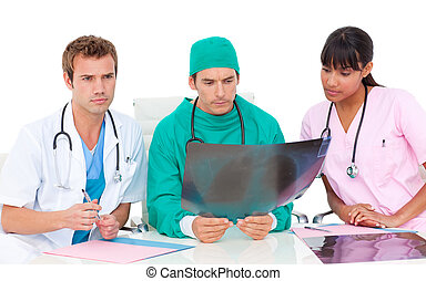 Serious medical team looking at X-ray - Serious medical team...