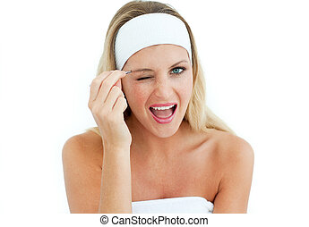 Young woman using tweezers against a white background