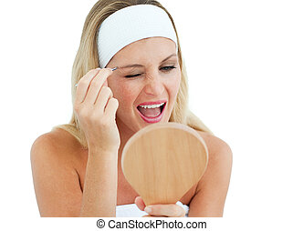 Blond woman using tweezers against a white background
