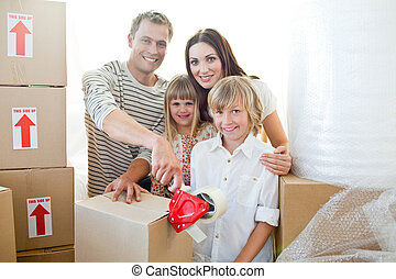Lively family packing boxes while moving house