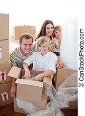 Happy family packing boxes while moving house