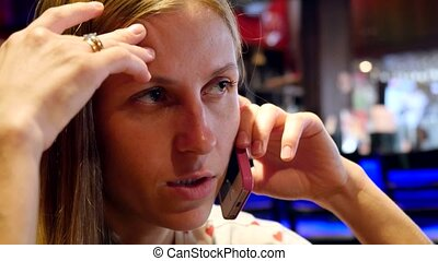 Young blond woman in cafe using her touchpad and answering phone call