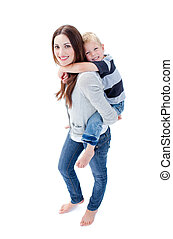 Brunette mother giving her son piggyback ride against a...
