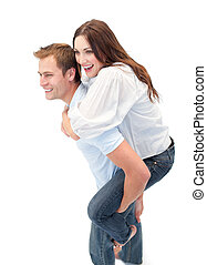 Radiant man giving his girl friend piggyback ride against a...
