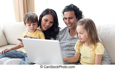 Affectionate parents using laptop with their children on...