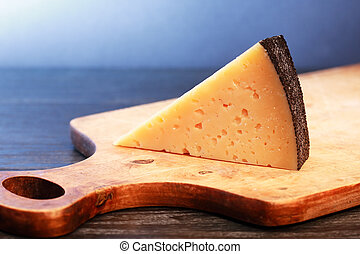 Hard Cheese - Piece of Gruyere cheese on wooden cutting...