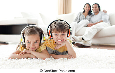 Adorable siblings listening music with headphones lying on...