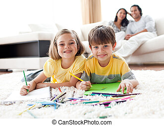 Beatiful siblings drawing lying on the floor in the living...