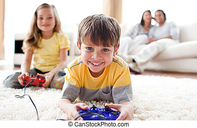 Cute little boy playing video game with his sister