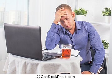 Businessman working in office, sitting at table with a laptop frowning and holding his head