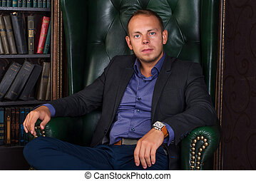 The man, calm and confident businessman sitting in a chair, library.