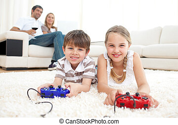 Keen siblings playing video games lying on the floor