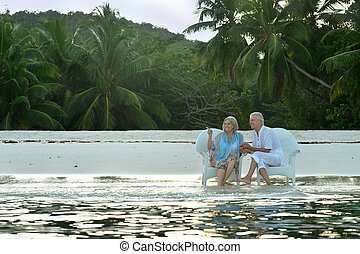 Elderly couple sitting on a background of palm trees
