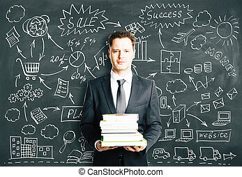 BUsinessman with books and concept strategy scheme on blackboard