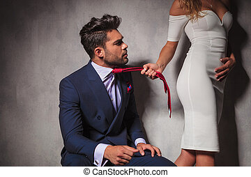 man looking at his lover while she pulls his tie - elegant...