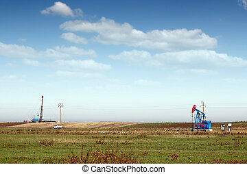 oil pump jack and land drilling rig on field