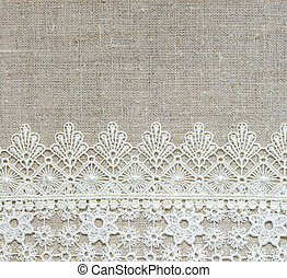 Textile background - White lace horizontal border over rough...