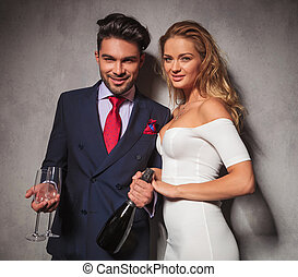 happy elegant couple holding a bottle of champagne and...