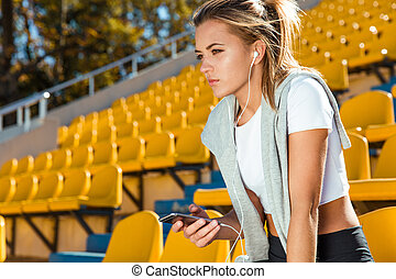 Fitness woman holding smartphone - Portrait of a a young...