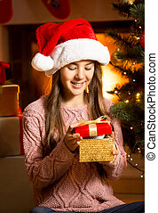 smiling girl posing with golden Christmas gift box -...