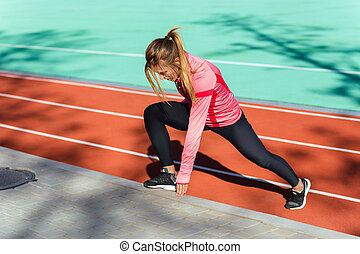 Woman doing stretching exercises at stadium - Portrait of a...