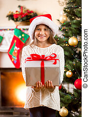 happy little girl holding big Christmas gift box - Portrait...