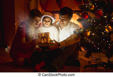 smiling family looking inside of glowing Christmas gift box...