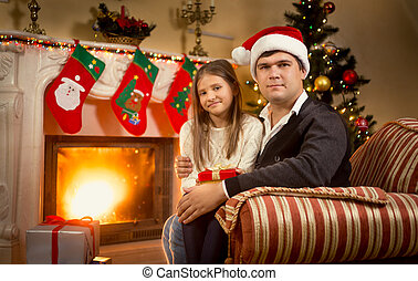 Portrait of father and daughter sitting on chair at fireplace