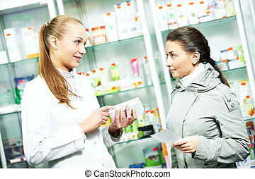 Pharmacy chemist consulting woman in drugstore