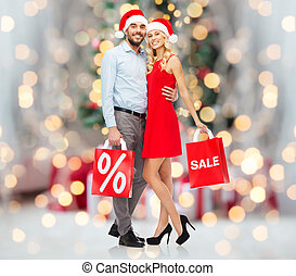 happy couple in santa hats with red shopping bags -...
