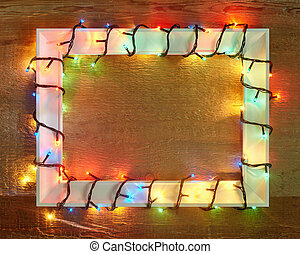 Christmas lights frame on wooden background with copy space