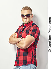 Handsome stylish man in sunglasses and hipster plaid shirt