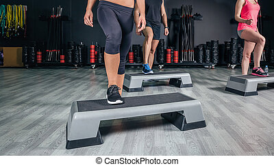 People legs over steppers training in aerobic class -...