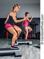 Women couple training over steppers in aerobic class - Women...
