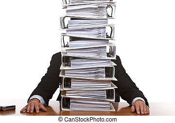 Business man sits in front of huge paperwork folders -...
