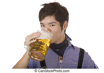 Young man drinking out of Oktoberfest beer stein Mass -...