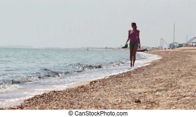 Beautiful girl goes on the beach the sea coast.