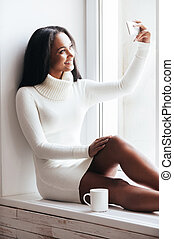 I love selfie! Beautiful young African woman in warm sweater...