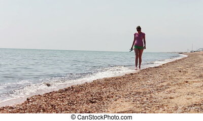 Beautiful girl goes on the beach the sea coast. - The girl...