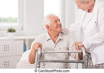 Using zimmer frame - Old man is using zimmer frame for...