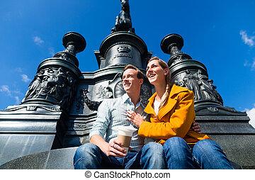 Couple sitting in Dresden Theaterplatz on statue