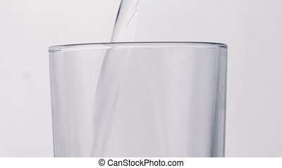 pouring water on glass on white background