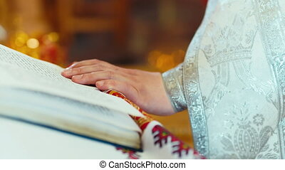 Hand the priest lying on open Bible