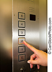 Woman in elevator or lift is pressing the button to get into...