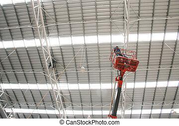 workers on orange boom lift repair roof - The atmosphere...