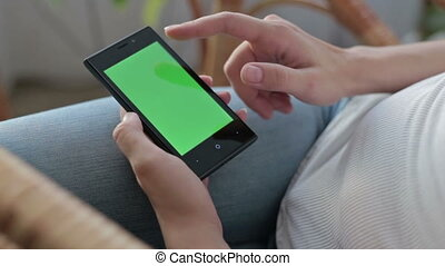 Woman hands touching and scrolling smartphone.green screen...